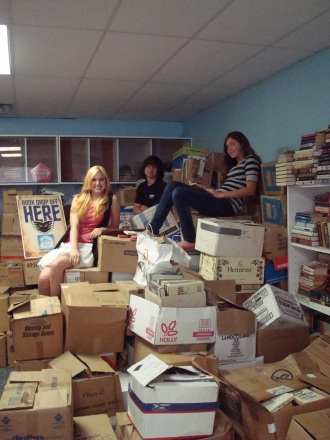 "Ashley, Matt and Christine McNeill take a well deserve break from sorting books for the Boys and Girls Club. They are pictured here on ""Mount Shakespeare"", aka our pile of unsorted donations."