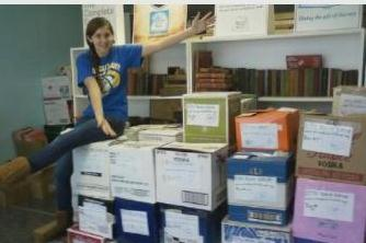 Epic Book Drive organizer Christine McNeill with some of the 60 boxes (so far!) ready to ship to New Orleans.