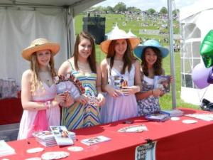 Success Won't Wait volunteers from H.B. duPont Middle School -- Claire Gonye, Shannon Martin, Christine McNeill and Alexandra Costantini show off some of the PONY USA books that were handed out at the annual Point-to-Point event.