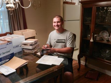 Success Won't Wait volunteer Matt McNeill, a sophomore at Archmere Academy, prepares 250 children's books for the Knollwood Community Center.