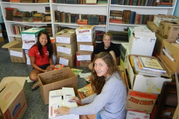 Left to right: Success Won't Wait volunteers Sophia Chen, Christine McNeill and Anna Gonye search for the perfect children's books to include for Wilmington Hospital.
