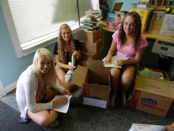 Success Won't Wait volunteers! Left to right:Addie Berger, Claire Gonye and Julianna Short work hard labeling children's books for Wilmington Hospital.