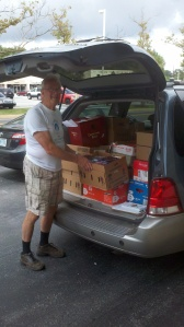 Larry Thurrell of the Friends of the Hockessin Library with some of the 800+ recently donated by Success Won't Wait!