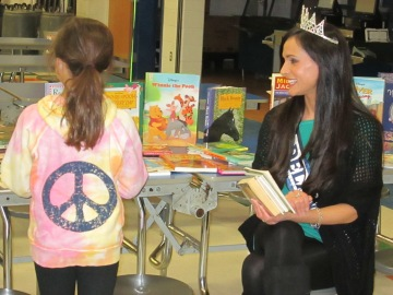 Vincenza Carrieri-Russo, Miss Delaware United States and the co-founder of Success Won't Wait, helps a students choose a book to keep at a recent North Star Elementary School event.