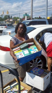 Desiree Faison, Youth Ministry and Community Service Coordinator at New Covenant Christian Fellowship with just a few of the books which will be given away on August 23!