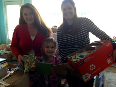 Left to right: Susan McNeill of Success Won't Wait, Grace Long, and Cristen Zipf of Treasures for Teachers with just a few of the more than 1,700 books donated to the organization.