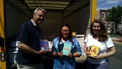 Showing off just a few of the books donated are volunteers Don McNeill and Susan McNeill with Aida Figueroa (center) of the Division of Family & Community Engagement at the Camden City School District.