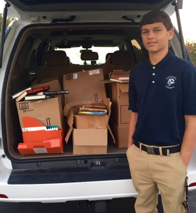 Caravel Academy freshman David Preziuso with some of the over 325 books he collected for Success Won't Wait literacy projects. Fall 2015.