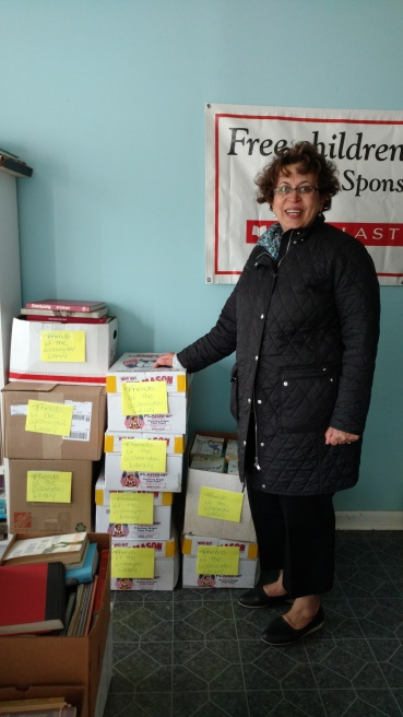 Neda Green of the Friends of the Wilmington Library with some of the 750 books donated by Success Won't Wait for the April Used Book Sale.