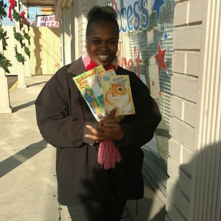 Representing Manna Academy for Learning is Ms. Parson with just a few of the over 850 children's books donated by Success Won't Wait.