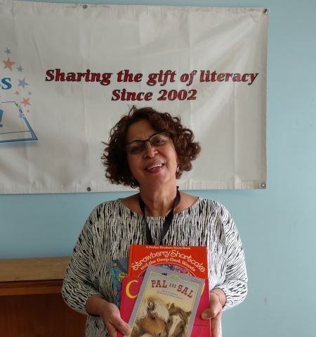 Neda Green of the Friends of the Wilmington Library with just a few of the 500 books provided by Success Won't Wait.